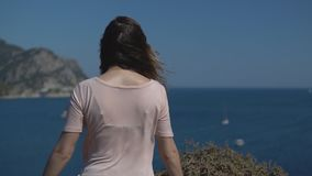People on holiday in warm countries. Rear view - an unidentified young girl in hat spread her arms out to admire freedom and nature on sunny summer day, slow stock video footage