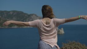 People on holiday in warm countries. Rear view - an unidentified young woman in hat spread her arms out to admire freedom and nature on sunny summer day, slow stock video footage