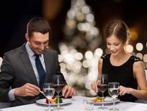 Smiling couple eating at christmas restaurant. People and holidays concept - smiling couple eating main course at restaurant over christmas tree background royalty free stock images