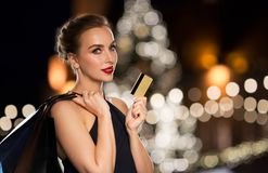 Woman with credit card and shopping bags. People, holidays, luxury and sale concept - beautiful woman with credit card and shopping bags over christmas tree Stock Photos