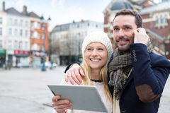 People on holidays visiting city helped by tablet Stock Photography