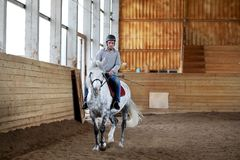 People on a horse training in a wooden arena Royalty Free Stock Photo