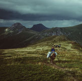 People on horseback, mountain blueberry pickers returning home Royalty Free Stock Photography