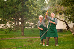 People with hose having fun. Cheerful senior couple in garden. Make it rain Stock Image