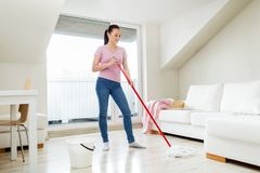Woman or housewife with mop cleaning floor at home. People, housework and housekeeping concept - happy woman or housewife with mop cleaning floor and dancing at Royalty Free Stock Photo