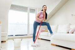 Woman or housewife with mop cleaning floor at home. People, housework and housekeeping concept - happy woman or housewife with mop cleaning floor and singing at Royalty Free Stock Image