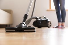 People, housework and housekeeping concept - happy woman with vacuum cleaner at home. Spring cleaning.  stock photography