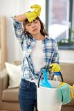 Tired woman with bucket and cleaning stuff at home royalty free stock photo