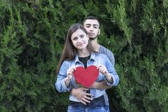 People hugging each other and holding red heart. Portrait of two charming people hugging each other and holding big red paper heart. Relationship, valentine and royalty free stock image