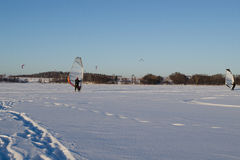 People ice sail surf  kiteboard snow lake  winter. Lot of people ice sailing surfing and kiteboarding on frozen Galves lake in Trakai amazing cold winter day Stock Images