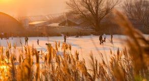 People ice skating on frozen lake during sunset Royalty Free Stock Photo