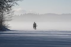 People icefishing on a lake in sweden. People icefishing on a little lake in sweden Royalty Free Stock Photography