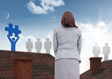 People icons with puzzle piece Businesswoman standing on Roofs with chimney and and blue sky Royalty Free Stock Photos