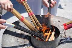 People ignite bundles of incense sticks royalty free stock images