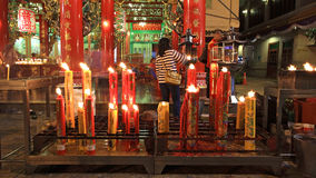 People incense near big candles to pray Stock Photo