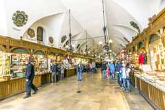People inside the Krakow Cloth Hall Sukiennice. KRAKOW, POLAND - MAY 4, 2014: People in a shopping arcade in the Krakow Cloth Hall Sukiennice. It dates to the Royalty Free Stock Images