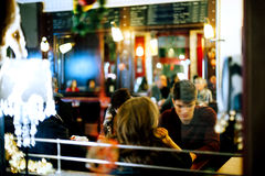 People inside restaurant having fun preparing for party Christma. STRASBOURG, FRANCE - DEC 20, 2016: View from street of people having fun inside restaurant cafe Stock Images