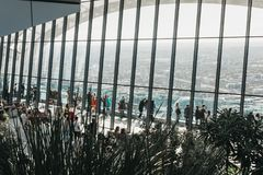 People inside Sky Garden, London, city skyline seen through the glass. Stock Photo