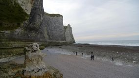 People inspect nude beach at low tide. Cloudy winter day in Etretat. France stock footage