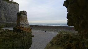 People inspect nude beach at low tide. Cloudy winter day in Etretat. France stock video