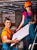 People installing suspended ceiling. People in builder uniform installing suspended ceiling stock images