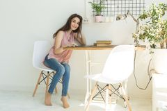 People, interior and technology concept - young woman sitting at a table with tablet at room.  stock photos