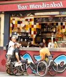 People in invalid prams, street bar. Stock Images
