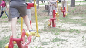 People Involved in Sports Training Apparatus on the Street. Children's Fitness Equipment on the Street. Many children are engaged in exercise in different stock video footage