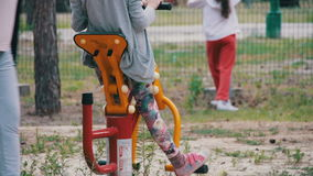 People Involved in Sports Training Apparatus on the Street. Children`s Fitness Equipment on the Street. Many children are engaged in exercise in different stock footage