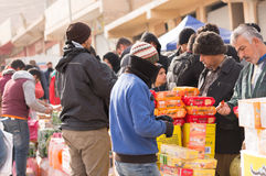 People on an Iraqi Market. People in an Iraqi market buying some biscuits. there are many kinds of bursitis in the photo, and it is clearly shot in the winter stock photography