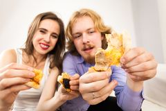 Couple eating pizza, having fun together. royalty free stock images