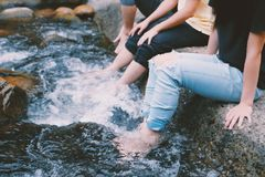 People In Jeans With Feet In Water Royalty Free Stock Photography