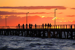 People on Jetty watching Sunset Stock Image