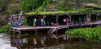 People on jetty welcoming the Aquidaban ship at Rio Paraguay. Rio Paraguay, Paraguay on August 5, 2015: Indigenous people make their way to the jetty to trade Stock Image