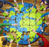 People with Jigsaw Puzzle Forming Globe in Photo Royalty Free Stock Images