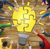 People with Jigsaw Puzzle Forming Light Bulb Stock Photography