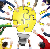 People with Jigsaw Puzzle Forming Light Bulb Royalty Free Stock Image