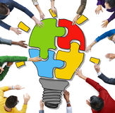 People with Jigsaw Puzzle Forming Light Bulb Stock Photos