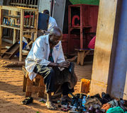 People. Jinja, Uganda - September 2015 - A roadside cobbler cleans a client's shoe. The cobbler, who seats at the roadside all day long, earns some really good Royalty Free Stock Photography