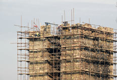 The people on the job, workers repaired the old fortress. With scaffolding and construction and protective helmets Stock Images