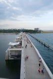 People jog and cycle on the bridge of Marina Barrage, Singapore Royalty Free Stock Photos