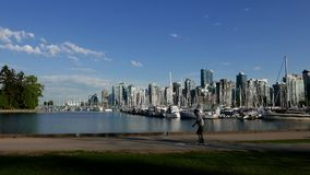 People jogging and riding bicycle in the Stanley park of the Vancouver downtown. Skyline and waterfront stock video