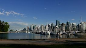 People jogging and riding bicycle in the Stanley park of the Vancouver downtown. Skyline and waterfront stock footage