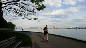 People jogging in the Stanley park of the Vancouver. Downtown skyline and waterfront stock video