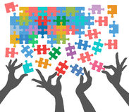 People join to find puzzle connections. Female hands work together to connect jigsaw puzzle pieces Royalty Free Stock Images