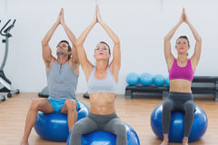 People with joined hands on exercise balls in gym Stock Photography