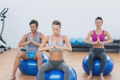 People with joined hands on exercise balls in gym Royalty Free Stock Photography