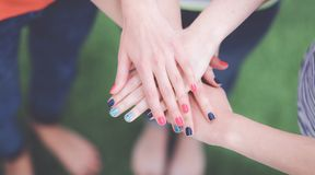 People joining their hands  on green grass Royalty Free Stock Images