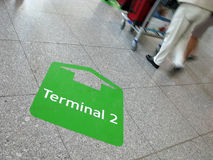 People on a journey at the airport. Sign arrow to terminal on the floor in airport with people on a journey Stock Photography