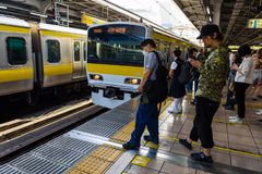 People at JR platform, Tokyo. Tokyo, Japan - May 8, 2017: Unidentified people at local Yellow and blue line JR platform with arrival trains Royalty Free Stock Photo